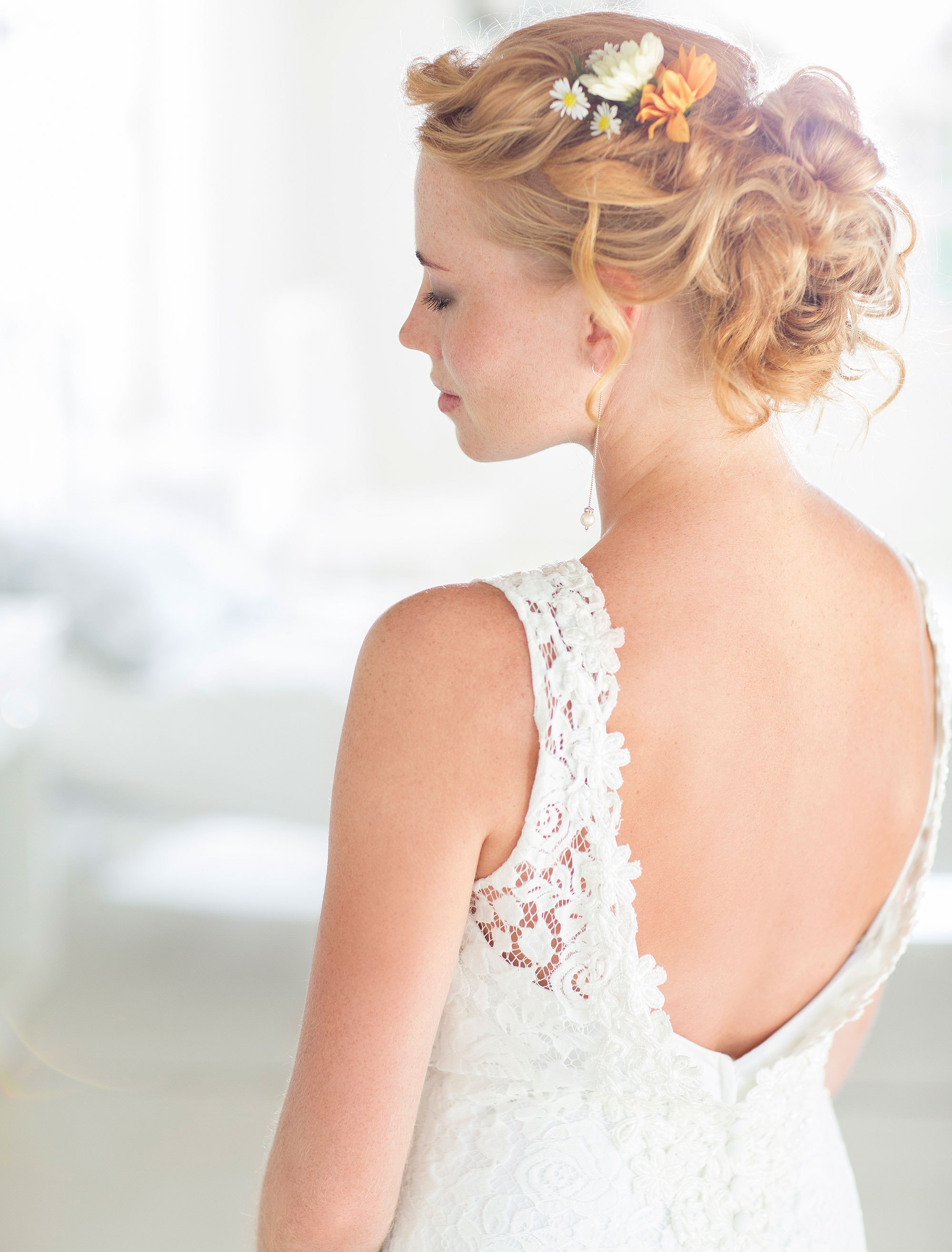 Young bride standing in sunny bedroom