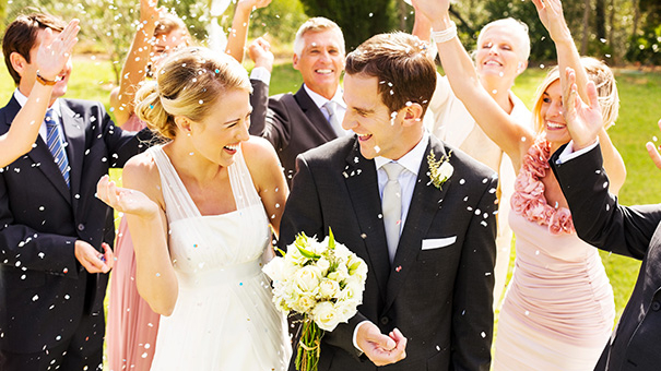 Happy wedding guests throwing confetti on couple during reception in garden. Horizontal shot.